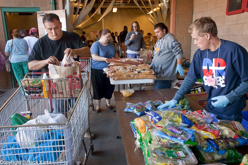 Apr. 3, 2009 -- MESA, AZ: TIM HALL, from Tempe, AZ, picks up fresh produce at the United Food Bank in Mesa, AZ. Hall said he drives a tourist bus but as the tourism and leisure industry has suffered in the recession his work in disappearing and in March he only work five days. A spokesperson for the United Food Bank in Mesa, AZ, said demand has increased by more than 100 percent in the last year. She said that at this time in 2008, about 175 people a week (the food bank is open one day a week) bought 200 boxes a food but now they were seeing about 350 people per week and they were buying 400-450 boxes of food per week. Each box of food cost $16 and contains enough food for five meals for two people, including meat, fruit and vegetables and starches. In addition to the food boxes, the food bank gives away perishables, like fresh baked goods and produce, that are donated by Phoenix area grocery stores and food producers. She said the number of donations to the food bank have increased as the economy has worsened but each donation is smaller and the gap between donations and what the food bank needs is widening.    Photo by Jack Kurtz / ZUMA Press