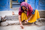 Jodhpur.  A brightly coloured hindu woman peforms puja, wearing yellow and red against a blue wall.