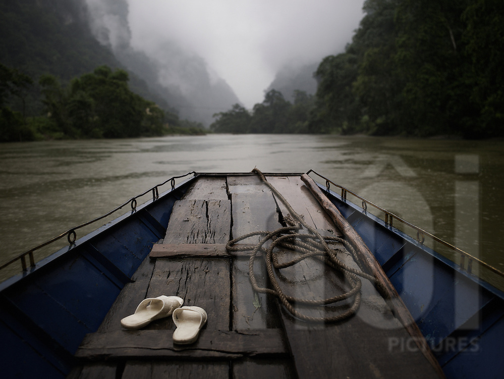 Front view of a small barge sailing on a river by a rainy day. Ba Be lake, Vietnam, Asia