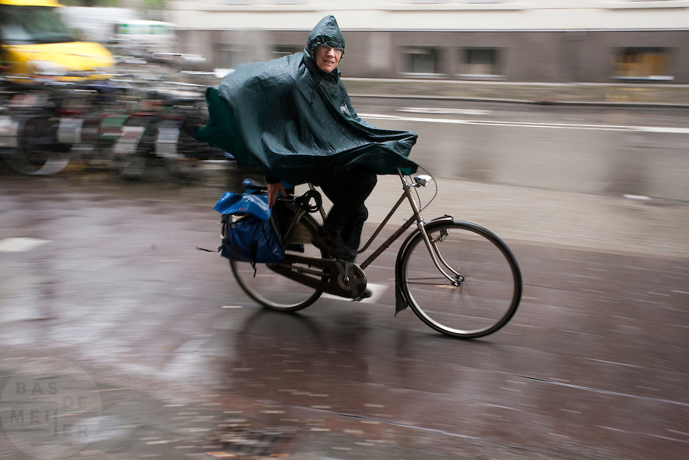 Fietsers rijden door de regen.<br /> <br /> Cyclists are riding in the rain.