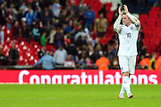 England's Wayne Rooney applauds the fans in front of a congratulations pitchside advertising board following him breaking the record for top interational goalscorer for England at the final whistle of the UEFA European 2016 Qualifying match between England and Switzerland at Wembley Stadium, London, England on 8 September 2015. Photo by Shane Healey.