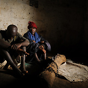 Mentally unwell patients of Kanye witch doctor, Alusine Kamara, in the room where they are confined. When the witch doctor deems it necessary, they may be chained to the log before them - scars on their ankles attest to this. The witch doctor says demons are at the root of their ills, and claims to have the power to communicate and negotiate with the demons or, if necessary, battle them with demon allies.