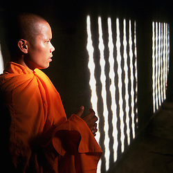 A buddhist monk reflects for a moment in the inner galleries of Angkor Wat, Cambodia.