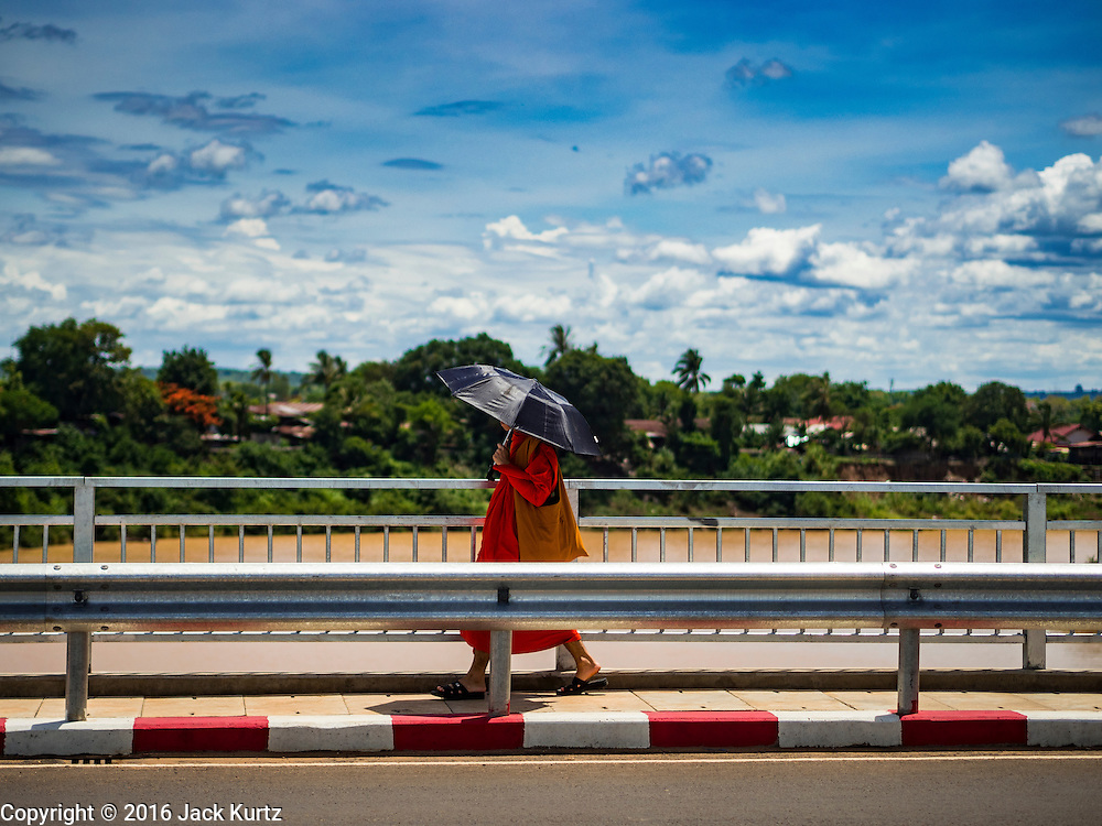 16 JUNE 2016 - PAKSE, CHAMPASAK, LAOS: A Buddhist monks walks across a bridge over the Xe Don River, which flows into the Mekong River in Pakse. Pakse is the capital of Champasak province in southern Laos. It sits at the confluence of the Xe Don and Mekong Rivers. It's the gateway city to 4,000 Islands, near the border of Cambodia and the coffee growing highlands of southern Laos.      PHOTO BY JACK KURTZ