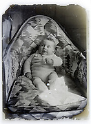 eroding glass plate with baby placed in a comfortable chair