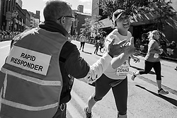 A member of the rapid responder team deployed with AED units near the finish line of the race, where a high number of cardiac events are likely to occur, high-fives a passing runner.