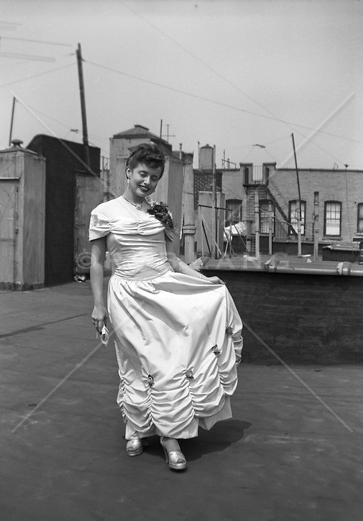Woman in a formal evening dress posing on a Bronx rooftop