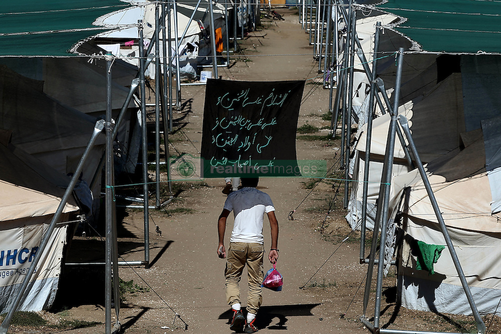 October 5, 2016 - Athens, Greece - A man walks among UNHCR tents, carrying food, in a sports facility at Helliniko Olympic complex in Athens, Greece on October 5, 2016.Almost 2,500 migrants and refugees, mainly Afghani, are housed at the former Athens airport site, and to an olympic complex used in the 2004 Olympics. In total 60.736 refugees and other migrants are stranded in Greece. (Credit Image: © Panayiotis Tzamaros/NurPhoto via ZUMA Press)