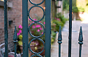 A wrought iron fence in front of a garden in New Orleans, Louisiana