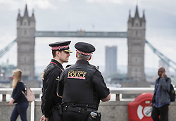 © Licensed to London News Pictures. 05/06/2017. London, UK. Police watch as people cross London Bridge for the first time after a terrorist attack on Saturday evening. Three men attacked members of the public after a white van rammed pedestrians on London Bridge. Ten people including the three suspected attackers were killed and 48 injured in the attack. Photo credit: Peter Macdiarmid/LNP