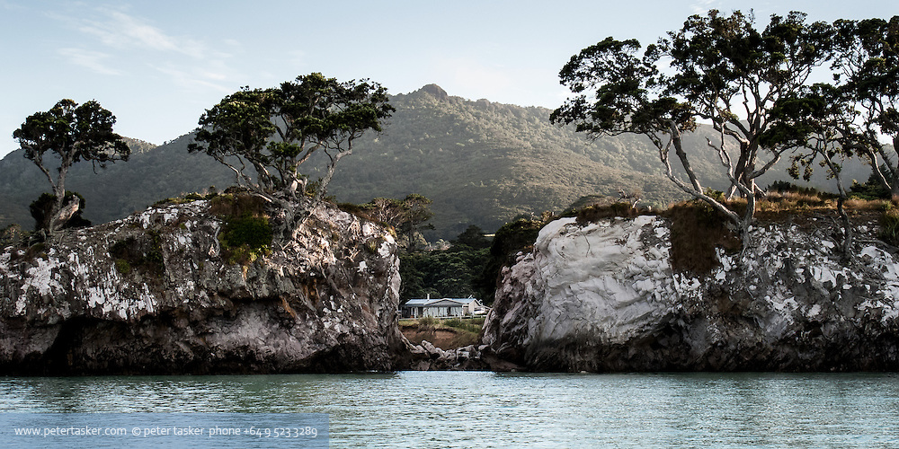 A house peeping through gap in small rock cliff face. Tryphena Harbour, Great Barrier Island, New Zealand.