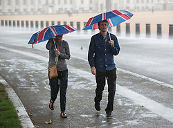 © Licensed to London News Pictures. 12/07/2016. London, UK. Visitors to London carry Union Jack flag umbrellas as a sudden rain storm hits central London. Photo credit: Peter Macdiarmid/LNP