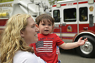 Merrick, New York, U.S. - May 26, 2014 - Mother holds her 2-year-old son who is pointing to a Fire Engine in the Merrick Memorial Day Parade, hosted by American Legion Post 1282 of Merrick, honoring those who died in war while serving in the United States military.