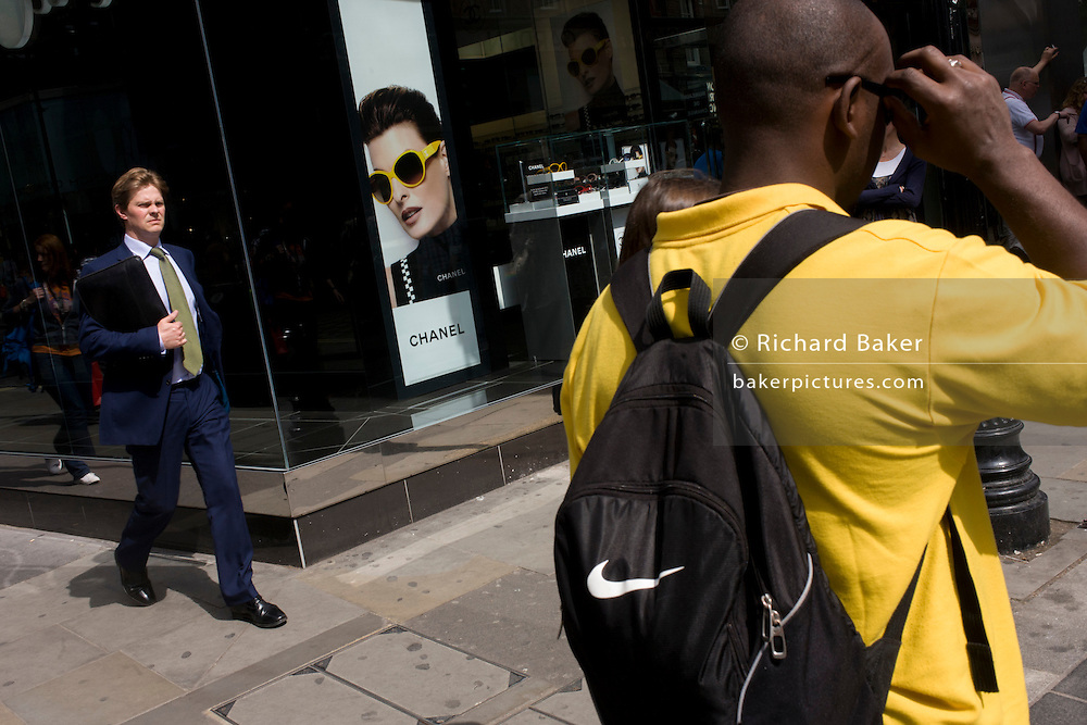 Men walk past a Chanel shop selling the latest in their range of sunglasses.