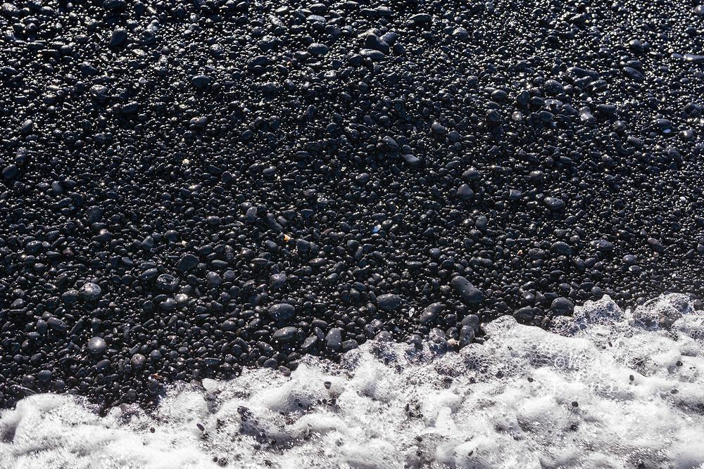 A wave washing up on the black rocks at Kiholo Bay, Big Island (Hawaii Island), Hawaii