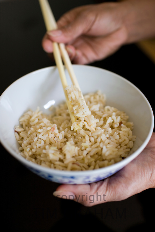 Asian woman holds bowl of brown wholegrain rice and chopsticks. Rice has become an expensive commodity as its in short supply.