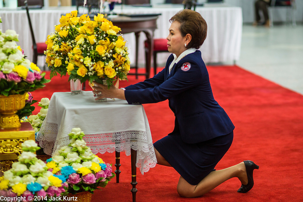 09 OCTOBER 2014 - BANGKOK, THAILAND: A representative of the Thai Red Cross leaves flowers for Bhumibol Adulyadej, the King of Thailand in the lobby at Siriraj Hospital. The King has been hospitalized since Oct. 4 and underwent emergency gall bladder removal surgery Oct. 5. The King is also known as Rama IX, because he is the ninth monarch of the Chakri Dynasty. He has reigned since June 9, 1946 and is the world's longest-serving current head of state and the longest-reigning monarch in Thai history, serving for more than 68 years. He is revered by the Thai people and anytime he goes into the hospital thousands of people come to the hospital to sign get well cards.   PHOTO BY JACK KURTZ