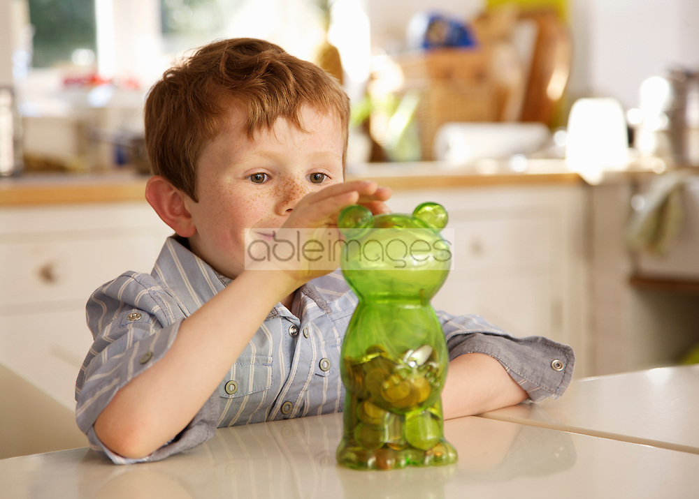 Boy putting coins into a money box in the shape of a teddy bear
