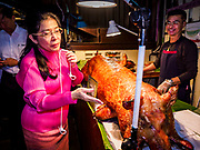 05 JANUARY 2019 - MINBURI, BANGKOK, THAILAND: SUDARAT KEYURAPHAN (pink blouse, left), the Pheu Thai Party candidate for Prime Minister of Thailand, looks at a whole deep fried pig during voter outreach at the Kwan Riam Floating Market at Wat Bamphen Nuea in Minburi, east of downtown Bangkok. The Thai government has tentatively scheduled a general election for 24 February 2019. It will be Thailand's first election since a military coup overthrew the government of Yingluck Shinawatra in 2014. Yingluck was a the leader of the Pheu Thai Party before her ouster. Sudarat was a member of Thaksin Shinawatra's cabinet. Thaksin's government was also deposed by a coup in 2006.       PHOTO BY JACK KURTZ