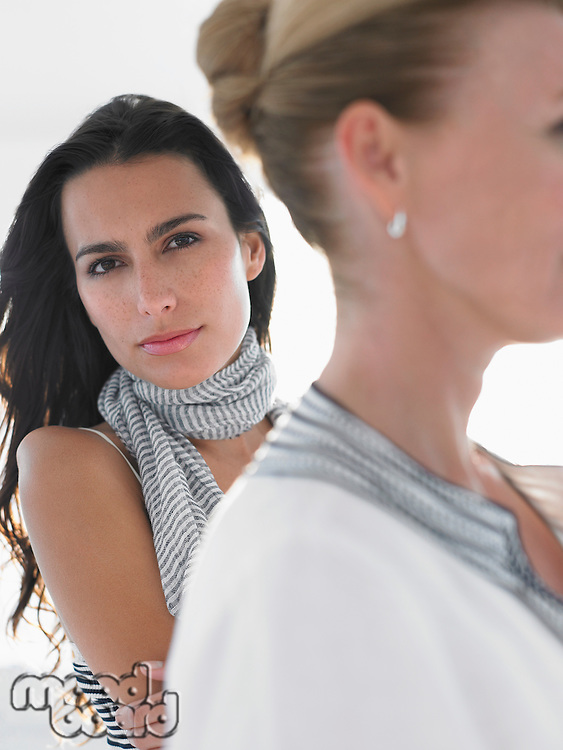 Two women outdoors focus on young woman looking at camera