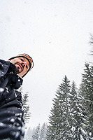 A man from a low angle with snow falling from the sky above him.