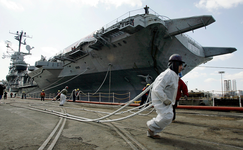 In this photo provided by the Intrepid Sea, Air & Space Museum, line handler Rafael Ramero carries the lines as the Intrepid aircraft carrier moves into the dry dock at Bayonne Dry Dock & Repair Corp. in Bayonne, N.J., to begin the first stage of its refurbishment, Tuesday, April 10, 2007. The Intrepid is expected to be in dry dock for approximately 60 to 75 days while it's hull and flight deck are repainted. (AP Photo/Intrepid Sea, Air & Space Museum/Stuart Ramson)