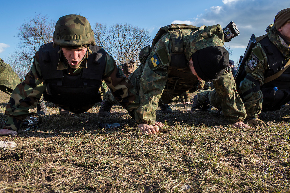 Members of the Azov Brigade do push-ups during weapons training at one of the group's training grounds on Saturday, March 7, 2015 in Kulykivske, Ukraine. Photo by Brendan Hoffman, Freelance