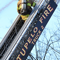 A fireman makes his way up the laddder to help fight a fire on Walker Street Monday.