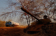 A pipe truck drives near an old military tank abandoned  by the side of the road between Juba and Bor in South Sudan, a reminder of the long years of civil war.  (PHOTO: MIGUEL JUAREZ LUGO)