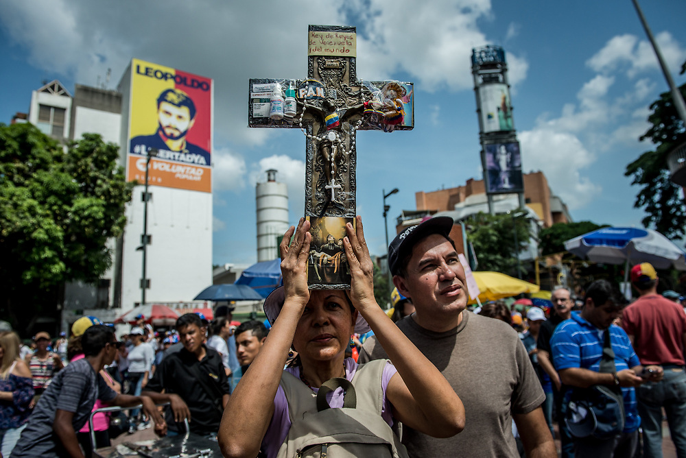 CARACAS, VENEZUELA - MAY 27, 2017: Priests, nuns and hundreds of other Catholics participate in a peaceful protest against government violence in Caracas. The streets of Caracas and other cities across Venezuela have been filled with tens of thousands of demonstrators for nearly 100 days of massive protests, held since April 1st. Protesters are enraged at the government for becoming an increasingly repressive, authoritarian regime that has delayed elections, used armed government loyalist to threaten dissidents, called for the Constitution to be re-written to favor them, jailed and tortured protesters and members of the political opposition, and whose corruption and failed economic policy has caused the current economic crisis that has led to widespread food and medicine shortages across the country.  Independent local media report nearly 100 people have been killed during protests and protest-related riots and looting.  The government currently only officially reports 75 deaths.  Over 2,000 people have been injured, and over 3,000 protesters have been detained by authorities.  PHOTO: Meridith Kohut