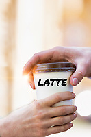 Close up photo of businesswoman giving businessman a cup of coffee latte