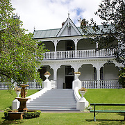 Alberton Historic House. Auckland. A Timber mansion began as a farmhouse in 1863 and was later expanded to 18 rooms, with fairy-tale decorative verandahs and towers. It was owned by the Kerr Taylors, a leading family in Mount Albert, until it was left to the New Zealand Historic Places Trust in 1972. Allan Kerr Taylor was a landowner, investor and provincial and local body politician. His wife Sophia was an outspoken advocate of the vote for women, as well as a singer, gardener and mother of 10. She ran the estate for 40 years after her husband's death, with her three unmarried daughters running it for a further 40 years..Alberton was famous in the 19th century for its balls, hunts, garden parties and music. It contains a wealth of original family furniture and other possessions, and several rooms retain their 19th century wallpapers. Alberton Historic House is situated in Mount Albert Road, Auckland, New Zealand.12th November 2010. Photo Tim Clayton.