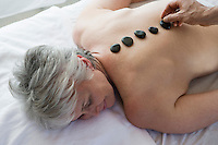 Senior woman having stone therapy