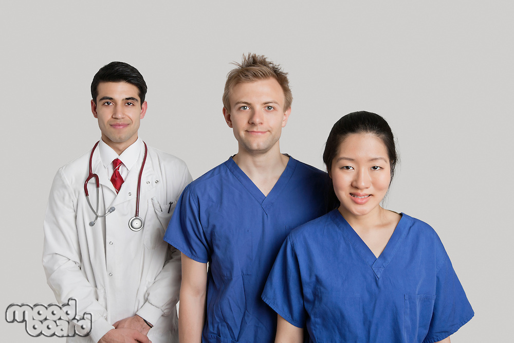 Portrait of happy medical team standing over gray background