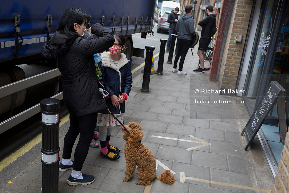 As the second week of the Coronavirus lockdown continues around the capital, and the UK death toll rising by 563 to 2,325, with 800,000 reported cases of Covid-19 worldwide, in accordance with the government's advice for social distancing and non-essential lockdown, a lady puts on her face mask while queueing with two children and an attentive poodle outside a local cafe in Herne Hill, on 1st April 2020, in London, England.