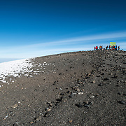 A group of climbers pose for photos next to the sign marking the summit of Mt Kilimanjaro (Uhuru Peak or Kibo Summit) (19,341 feet).