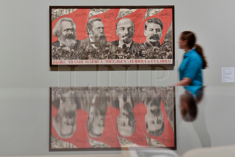 "© Licensed to London News Pictures. 07/11/2017. London, UK.  A student from Thomas Tallis School, Kidbrooke, south London, walks by ""Under the Banner of Marx, Engels, Lenin and Stalin!"", 1933, by Gustav Klutsis, at a preview of ""Red Star Over Russia: A Revolution in Visual Culture 1905-55"" at Tate Modern.  The exhibition marks the centenary of the October Revolution and presents the visual history of Russia and the Soviet Union with works drawn from the late graphic designer David King. Photo credit: Stephen Chung/LNP"