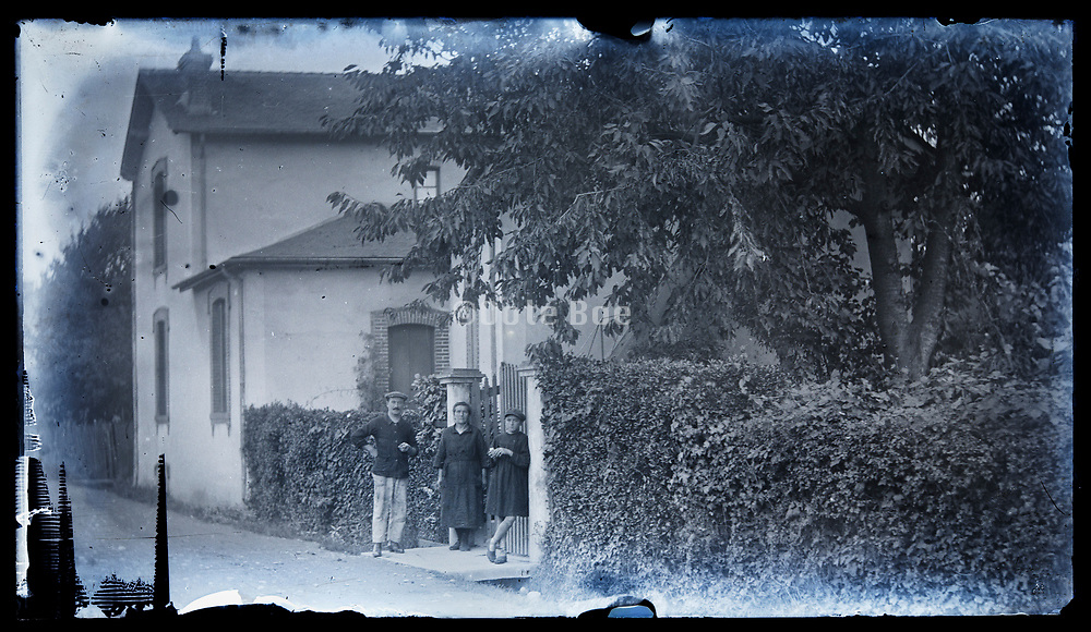 adult people standing by house entrance gate France circa 1930s