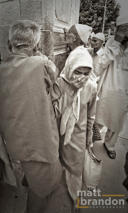 Girls weeps as a man kisses the shrine for a blessing.