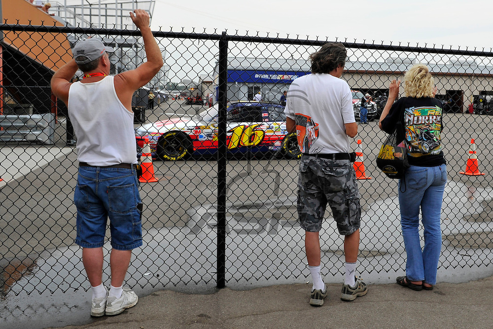 Brooklyn, MI - JUN 16, 2012:  Fans watch the cars in the garage during practice for the Quicken Loans 400 race at the Michigan International Speedway in Brooklyn, MI.
