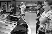 Tired junior flyers wait for their baggage at SeaTac airport, after an evening flight.