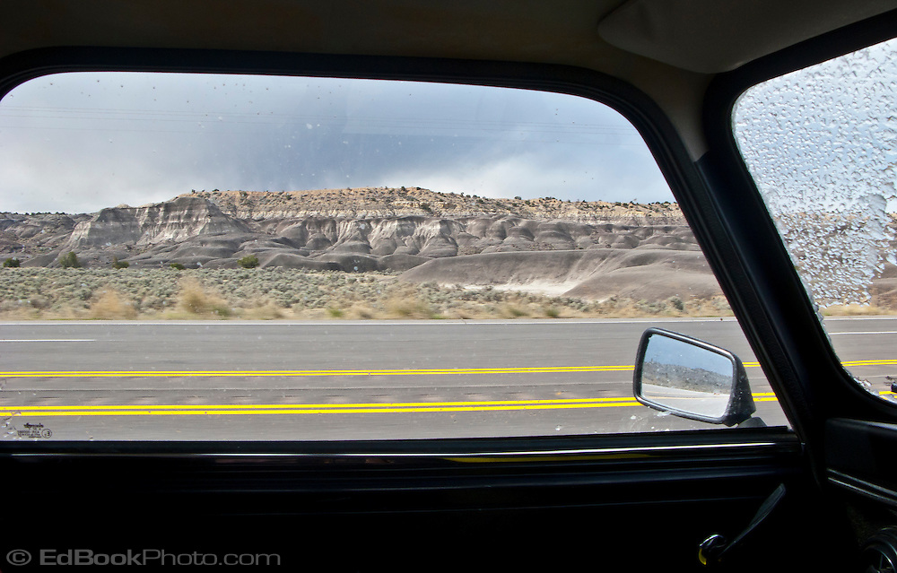 an eroded rock formation in rural NW New Mexico along US 550 is framed with parallel yellow painted highway lines through a window of a classic Mini Cooper automobile and snow on the adjacent windshield