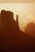 The Mittens face off in a dust storm. Monument Valley, Arizona.