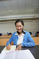 Mature female student working in lecture theatre, portrait