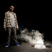 A man stands next to a skateboard with smoke coming from underneath it at night.