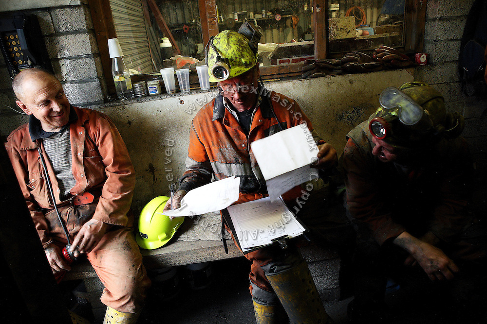 (left to right) Tony Berg, 58, Vernon Watkins, 62, and Keith Aubrey, 56, three of the miners working to restore Unity Mine are portrayed at the end of their shift while having a chat and compiling the daily operations report, on Wednesday, Apr. 11, 2007, in Cwmgwrach, Vale of Neath, South Wales. The time is ripe again for an unexpected revival of the coal industry in the Vale of Neath due to the increasing prize and diminishing reserves of oil and gas, the uncertainties of renewable energy sources, and the technological advancement in producing energy from coal while limiting emissions of pollutants, has created the basis for valuable investment opportunities and a possible alternative to the latest energy crisis. Unity Mine, in particular, has started a pioneering effort to revive the coal industry in the area, reopening after more than 8 years with the intent of exploiting the large resources still buried underground. Coal could be then answer to both, access to cheaper and paradoxically greener energy and a better and safer choice than nuclear energy as a major supply for the decades to come. It is estimated that coal reserves in Wales amount to over 250 million tonnes, or the equivalent of at least 50 years of energy supply, while the worldwide total coal could last for over 200 years as a viable resource compared to only a few decades of oil and natural gas.