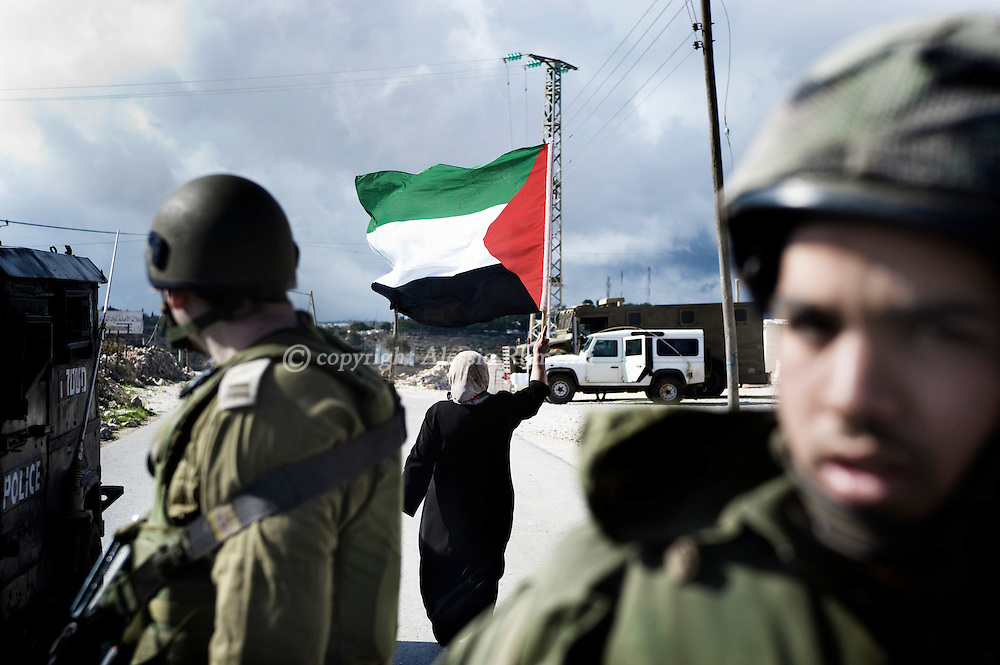 A Palestinian woman waves her national flag behind Israeli soldiers during a protest against Israel's controversial separation barrier in the West Bank village of Maasarah, near Bethlehem, on November 13, 2009..© ALESSIO ROMENZI