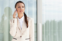 Businesswoman answering cell phone by glass door