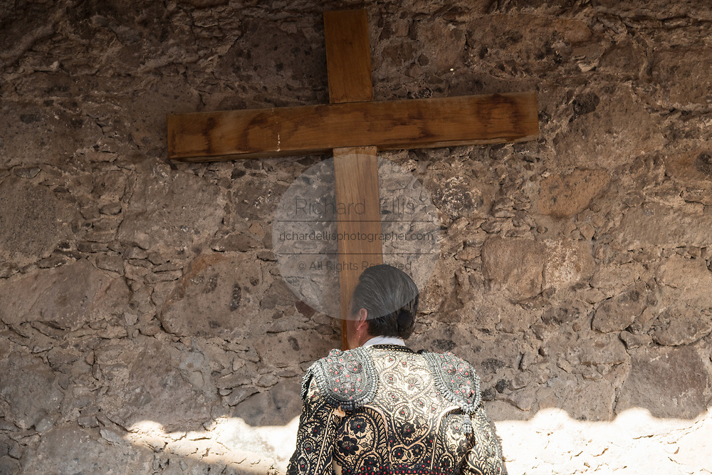 A Mexican Matador kisses the cross at a small chapel before entering the bull ring for the bullfights at the Plaza de Toros in San Miguel de Allende, Mexico.