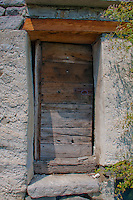 Close-up of an old wooden door and lintel in a stone building in Ticino, Switzerland.